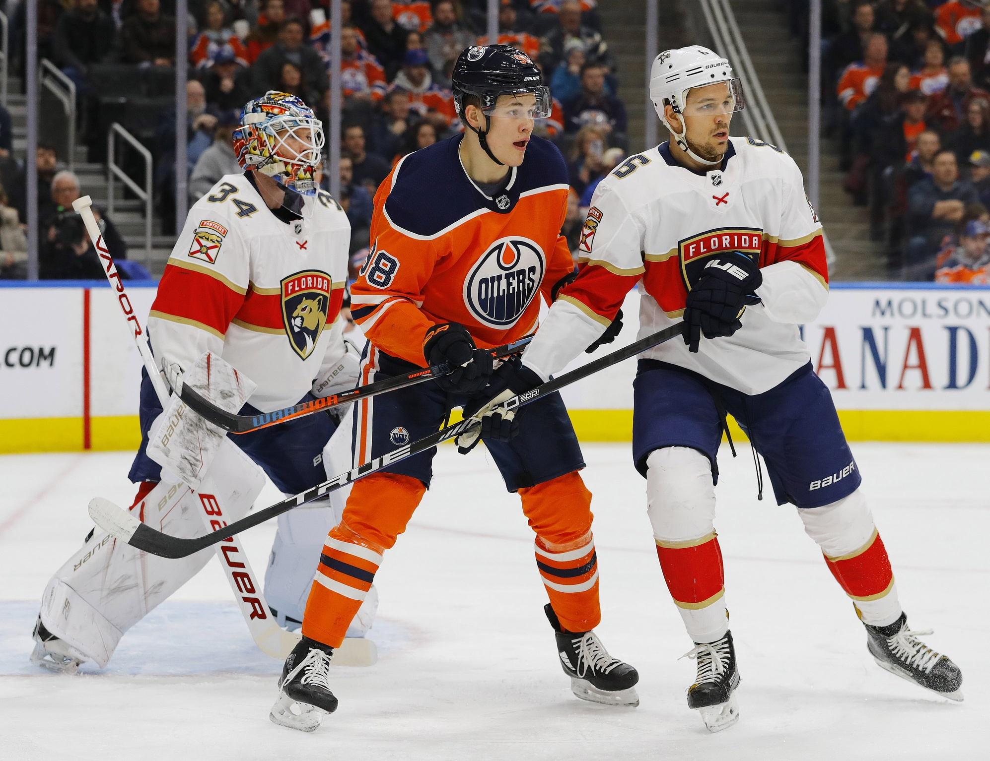 Jesse-puljujarvi-oilers-battles-with-alex-petrovic-panthers-in-front-of-james-reimer